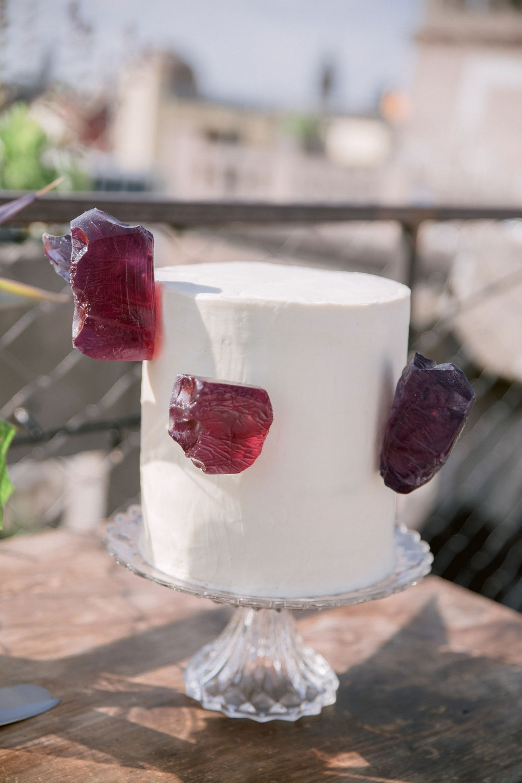 White wedding cake with purple glass pieces made from jelly