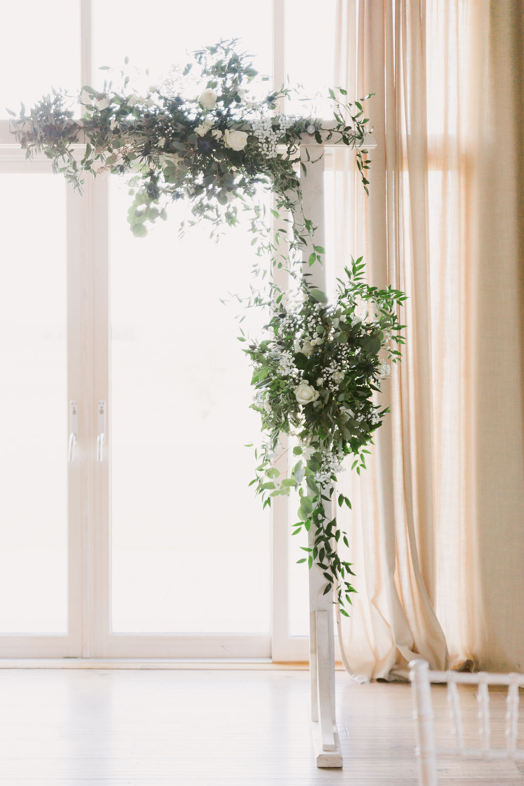 White wedding arch with green flowers | Barra Castle Wedding