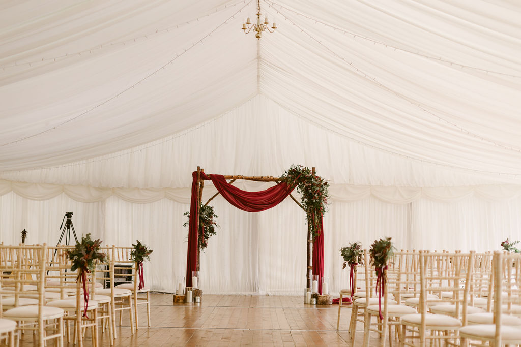 Elsick House Wedding | Marquee Wedding at Elsick House decorated in burgundy | Birch Ladder wedding arch with draped fabric | Elsick House Aberdeen Wedding Ceremony Location