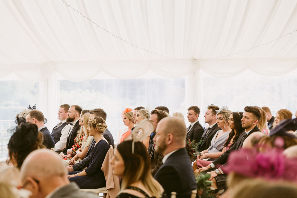 Wedding guests seated in marquee